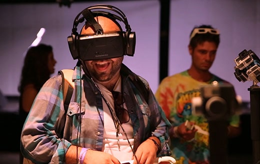 a man at a conference laughing while wearing a virtual reality headset