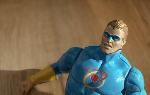animated super hero action figure lying on hardwood floor