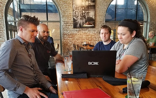 a group of people at a restaurant all looking at the screen of a BOXX laptop