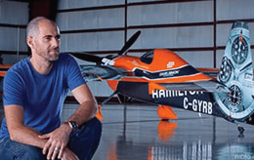 Daniel Simon sitting with one of his race car designs
